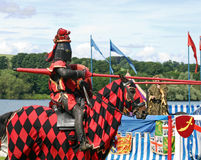 Knight on horseback. The red knight of old                       on horse back jousting in full armour Stock Photo