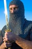 Knight l'armatura da portare e tenga su una spada fotografie stock libere da diritti