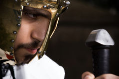 Knight looking at his sword. Knight with gold helmet looking at his sword Stock Photography