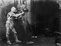 Knight at the movies, a man in an armored suit uses a film camera Stock Photography