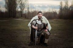 Knight na armadura com uma espada em suas mãos fotografia de stock