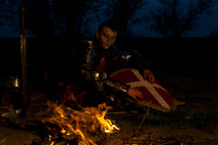 Knight near the fire. Knight have a warm near the fire at night Royalty Free Stock Photo