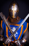 Knight is posing. Warrior holding his weapons in hands Royalty Free Stock Image