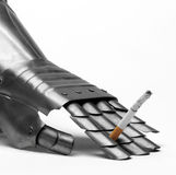 Knight's glove whit smoking cigarette Royalty Free Stock Images