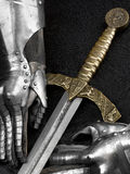 Knight's gloves and sword. Stock Photos