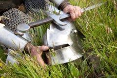 Knight's hands, helmet,  sword. Knight's helmet and sword / wet after rain Royalty Free Stock Images