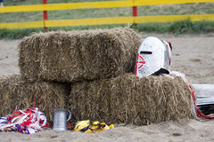 Knight's helmet and cup. A stein and helmet are laying on a bale of hay Stock Images