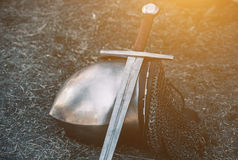 Knight`s helmet and shiny metal lying on the ground, it put an old steel sword with leather handle Stock Image