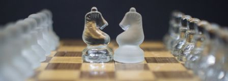 A Knight`s stand off, Icy Knight chess pieces on a black background royalty free stock images