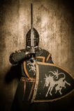 Knight with shield. Medieval knight  holding sword in front of his face Royalty Free Stock Images