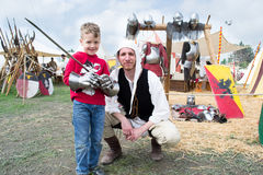 Knight shows the parts of medieval armor to a child Stock Image
