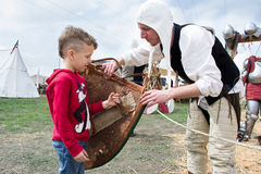 Knight shows the shield to a child Stock Photos