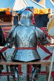 Knight with silver helmet sitting on chair.  Royalty Free Stock Images