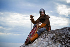 Knight sitting on a rock with a sword Royalty Free Stock Images