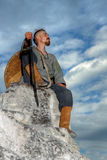 Knight sitting. On a rock with a sword against blue cloudy sky Stock Photos