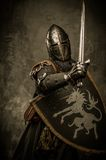 Knight with sword. Medieval knight in attack position Stock Photo
