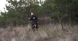 Knight with a sword comes out of a pine forest. At dusk stock footage