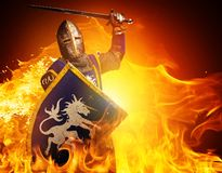 Knight with a sword in flame. Medieval knight in attack position on fire background Stock Photo