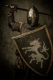 Knight with sword and shield. Medieval knight on grey background Stock Photography