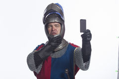 Knight taking picture with smartphone, horizontal. Knight taking picture with smartphone. (Are you in the dark ages when it comes to technology Royalty Free Stock Photos