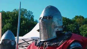 Knight toernooien Ridder vóór de strijd Mens in ijzerpantser met zwaard in handen tegen de blauwe hemel