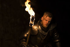 Knight with a torch at night on a wall background. Knight with a torch at night after the battle. Adventure stock images