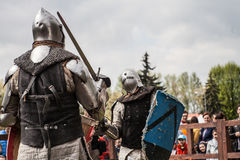Knight tournament. The knights in the congregations are fighting in the ring. Public event in the city. Soldiers in armor of the Middle Ages Royalty Free Stock Photo