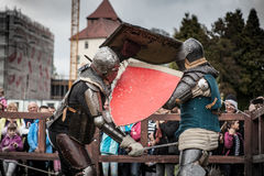 Knight tournament. The knights in the congregations are fighting in the ring. Public event in the city. Soldiers in armor of the Middle Ages Stock Images
