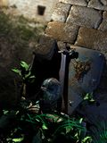 Knight treasures among ruins. Sword, shield and helmet of a medieval knight, among the ruins of a castle Stock Image