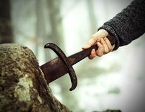Knight tries to remove Excalibur sword in the stone. Hand of the valiant knight tries to remove the magical Excalibur sword in the stone Stock Images