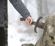Knight tries to remove Excalibur sword in the stone. Hand of the valiant knight tries to remove the magical Excalibur sword in the stone Royalty Free Stock Image