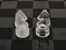 Knight Watch. Knights of a different color face off on a clear glass etched chess board Stock Photography