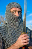 Knight wearing armour and hold on a sword stock image