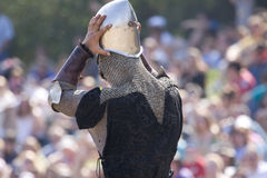 Knight wearing helmet. A knight is putting his helmet on Royalty Free Stock Images