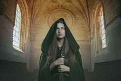 Knight woman with sword. Knight woman with mediaeval sword. Stone castle background stock image