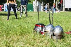 Knightly hełmy kłamają na trawie przeciw tłu bojów ludzie zdjęcie stock