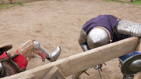 Knights in steel armor and chain mail helmets fighting at medieval tournament. 4k stock footage