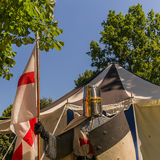 Knights templar. A person dresses up historically to mimic a knights templar in full armour standing in front of a white and blue tent holding a shield and flag Royalty Free Stock Image