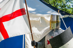 Knights templar. A person dresses up historically to mimic a knights templar in full armour standing in front of a white and blue tent holding a shield and flag Royalty Free Stock Images