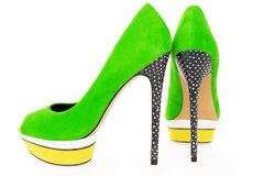 Knip van heldergroene en gele hoge hielschoenen op whit stock afbeelding