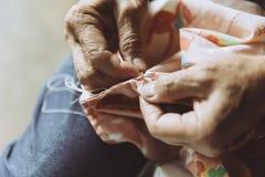 Knipa för reparation för kläder för sömnad för äldre hand för Closeup arkivfoton
