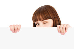 Knipogende vrouw die over leeg aanplakbord gluurt Stock Fotografie