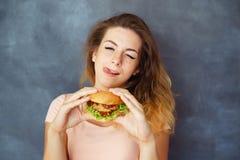 Knipogende vrouw met smakelijke hamburger in handen royalty-vrije stock afbeeldingen