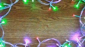 Knipperend kleurrijke slingers op houten achtergrond met ruimte voor tekst, kader van het knipperen van slingers stock videobeelden