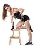 Knipselportret van spier jonge vrouw die een domoor voor de opleiding van haar achterspieren opheffen die op de stoel leunen Stock Afbeelding