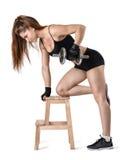 Knipselportret van spier jonge vrouw die een domoor voor de opleiding van haar bicepsen opheffen die op de stoel leunen stock foto's