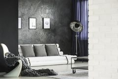Modern living room interior. Knit blanket on white chair in modern living room interior with posters above sofa with grey cushions Stock Image