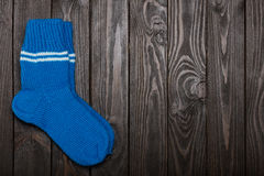Knit blue wool socks on dark wooden background. Stock Photos