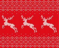 Knit christmas design with deers and ornament. Xmas seamless pattern red background. Knitted winter sweater texture. Royalty Free Stock Image