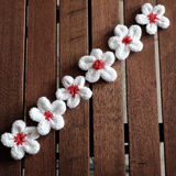 Knit daisy flower on wood background Royalty Free Stock Image